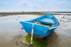 Um barco de pesca velho amarrado encalhou na praia na maré baixa Foto de Stock