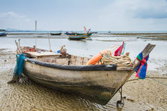 Um barco de pesca velho amarrado encalhou na praia na maré baixa Imagens de Stock