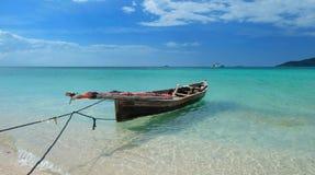 Um barco de pesca velho pela praia em uma água azul clara fotografia de stock royalty free