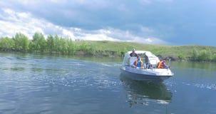 Um barco de prazer com dois povos a bordo está chegando O barco de motor moderno elegante está na doca no dia de verão do rio da  filme
