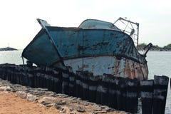 Um barco dilapidado do pescador em um porto pequeno indiano foto de stock