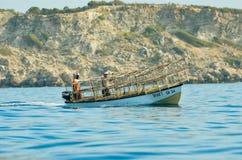 Um barco na água atrás dos penhascos fotografia de stock