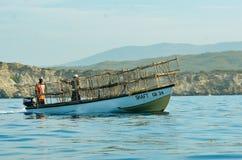 Um barco na água atrás dos penhascos imagem de stock royalty free