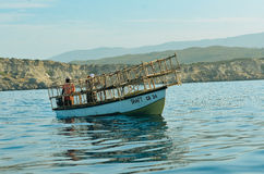 Um barco na água atrás dos penhascos imagem de stock