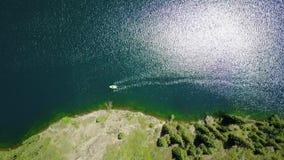Um barco no meio de um lago da montanha Lago da montanha da paisagem na floresta vídeos de arquivo