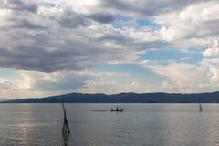 Um barco pequeno com alguns povos em um lago, abaixo de um bl bonito Imagens de Stock Royalty Free