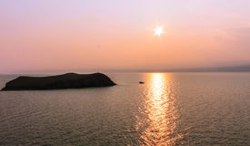Um barco só de flutuação que passa pela ilha no por do sol do por do sol, barco, ilha, lago, água, mar, rosa, laranja, noite, ver Fotografia de Stock