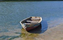 Um barco velho amarrado ao banco de rio Fotografia de Stock