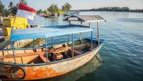 Um barco velho tradicional na água do mar azul da costa com a ilha verde na distância no jawa do karimun imagens de stock