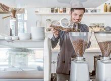 Um barista derrama feijões de café fotos de stock