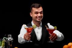 Um barman atrativo com dois vidros do margarita completamente dos cocktail, laranjas, limão, um abanador em um fundo preto Foto de Stock