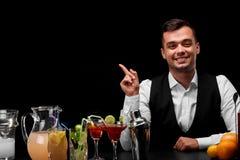 Um barman que aponta em algo, um contador com laranjas, limão da barra, um abanador, vidros do margarita no fundo preto Foto de Stock