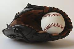 Um basebol em um Brown e em uma luva preta Imagem de Stock