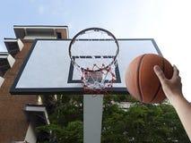 Um basquetebol do jogo do homem Opinião de baixo ângulo da aro de basquetebol contra no fundo branco Fotografia de Stock Royalty Free