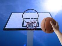 Um basquetebol do jogo do homem Opinião de baixo ângulo da aro de basquetebol contra o céu azul Fotos de Stock Royalty Free