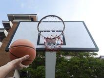 Um basquetebol do jogo do homem Opinião de baixo ângulo da aro de basquetebol contra o céu azul Fotografia de Stock Royalty Free