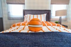 Um basquetebol na cama com a lâmpada de cabeceira no quarto caçoa imagem de stock