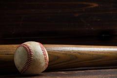 Um bastão de beisebol e uma bola de madeira em um fundo de madeira Foto de Stock