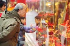 Um batente do homem a olhar no indicador de uma loja do ouro Fotos de Stock