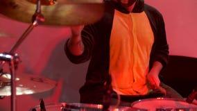 Um baterista em uma máscara joga cilindros em um concerto video estoque