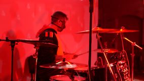 Um baterista em uma máscara joga cilindros em um concerto filme