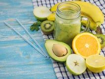 Um batido recentemente preparado do abacate, da banana, da laranja, do limão e do quivi em uma tabela de madeira azul Alimento do Imagens de Stock