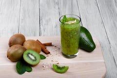 Um batido verde completo de vidro do fruto de quivi com sementes, o abacate, as nozes, canela e a hortelã pretos em uma luz de ma Fotografia de Stock