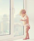 Bebé que olha para fora o desejando, a tristeza, e a espera da janela Fotos de Stock Royalty Free