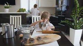 Um bebê bonito pequeno com cabelo longo no vestido branco sent-se-ar na mesa de cozinha e misturou a farinha quando sua mamã filme