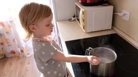 Um bebê bonito pequeno que cozinha o papa de aveia sobre na cozinha vídeos de arquivo