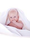 Um bebê bonito sob uma toalha branca Foto de Stock