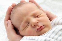Um bebê de sono bonito nas mãos Foto de Stock Royalty Free