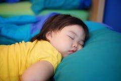 Um bebê de sono com sua cabeça que descansa em um descanso imagem de stock royalty free