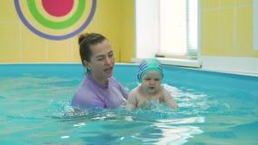 Um bebê do ano em sua primeira lição nadadora
