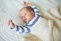 Um bebê do mês que encontra-se sob a cobertura feita malha imagem de stock