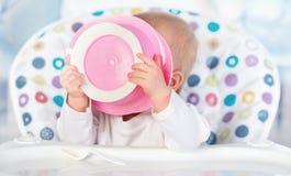 O bebê engraçado está comendo da placa cor-de-rosa Imagens de Stock Royalty Free