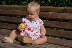 Um bebê está examinando uma maçã Imagens de Stock