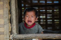 Um bebê Laotian que grita na janela de sua casa tradicional foto de stock