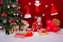 Um bebê maravilhoso nos pijamas olha presentes de Natal Fotografia de Stock Royalty Free