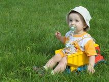 Um bebê no caminhão na grama Imagem de Stock