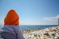 Um bebê olha na distância no lago Foto de Stock