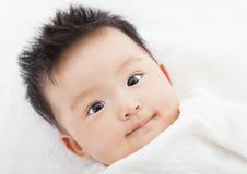 Um bebê pequeno bonito e sorrindo está olhando fotos de stock