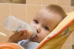 Um bebê pequeno está comendo o leite Fotos de Stock Royalty Free