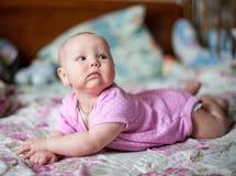 Um bebê pequeno nos clithes cor-de-rosa que encontram-se em casa na cama imagem de stock royalty free