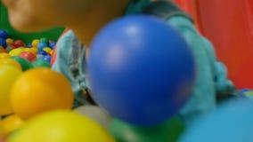 Um bebê pequeno que desliza na corrediça em uma associação da bola filme