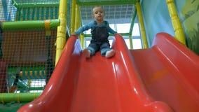 Um bebê pequeno que desliza na corrediça em uma associação da bola vídeos de arquivo