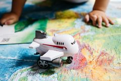 Um bebê pequeno que joga com um brinquedo dos aviões no mapa do mundo, mãos dos childs, curso com crianças imagem de stock