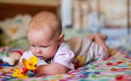 Um bebê pequeno que joga em uma cobertura imagens de stock royalty free