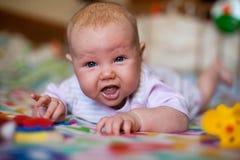 Um bebê pequeno que joga em uma cobertura fotos de stock