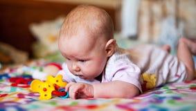 Um bebê pequeno que joga em uma cobertura imagem de stock royalty free